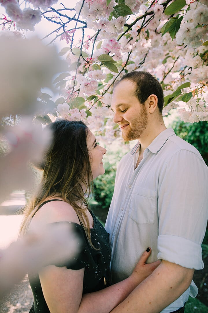 couple romantically gazing at each other under blossom trees in castle ashby's gardens