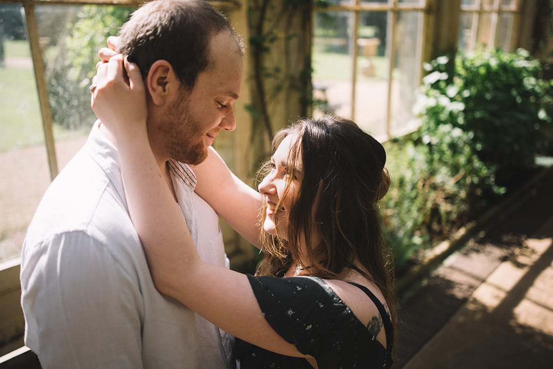 close up of Couple cuddling in front of a window in castle Ashby's orangey with greenery all around them during couple session